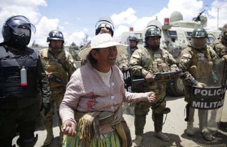 A woman protests in front of security personnel against the interim government of Jeanine Ãnez.
