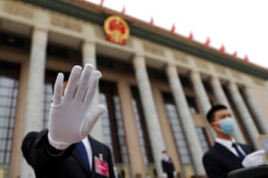 A security guard gestures at the photographer outside the Great Hall of the People in Beijing, China