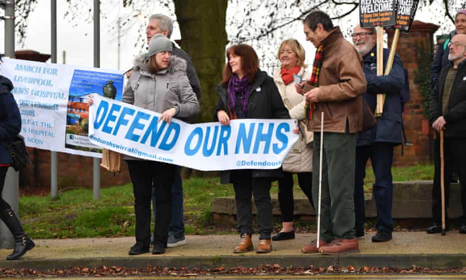 Protesters gather before Theresa May's visit to Alder Hey children's hospital in Liverpool on Monday.
