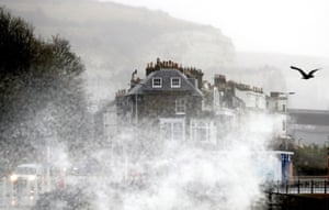 Waves crash over the promenade in Dover, Kent, during strong winds and rain