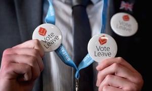A man holds Vote Leave badges