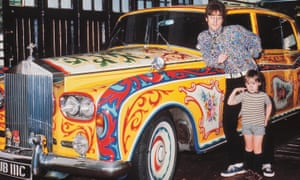 John Lennon and his young son Julian posing in his house's garage in front of his psychedelic Rolls Royce.