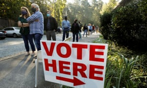 Voters wait in a 90-minute line to cast their ballots on the first day of the state's in-person early voting for the national elections in Durham, North Carolina, on 15 October.