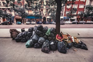 Virginia in street surrounded by black bags