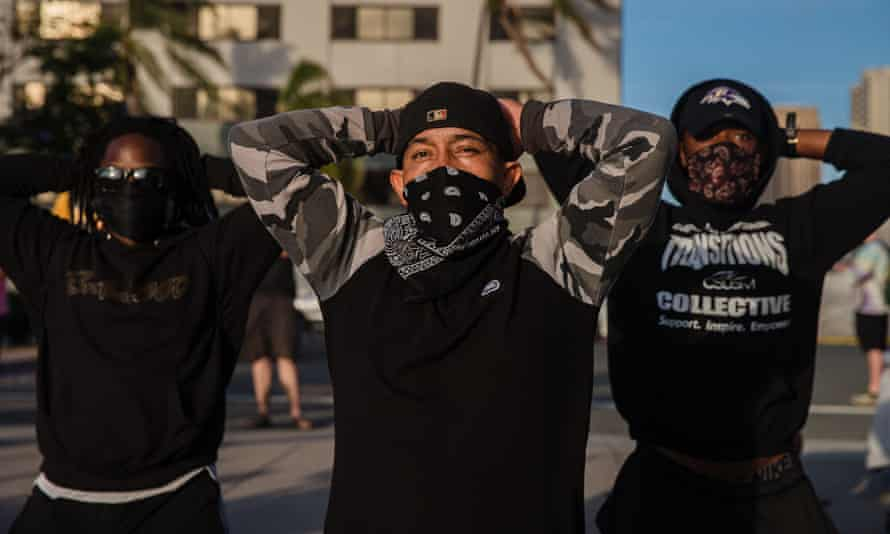 Demonstrators stand in front of San Diego police on Sunday.