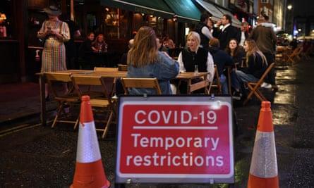 People drinking outside an establishment in Soho in London after dark.