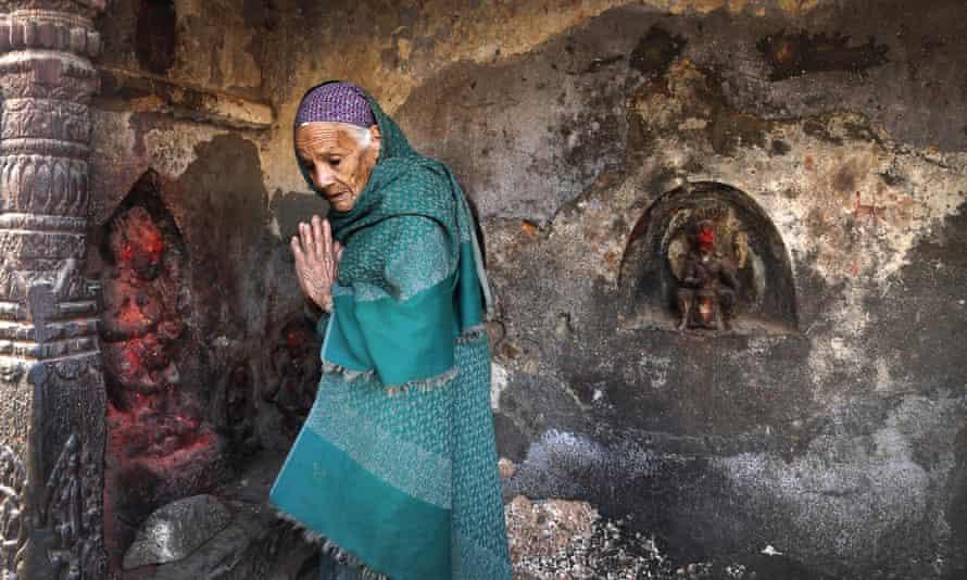 An elderly Nepalese woman prays at a damaged temple in Kathmandu.