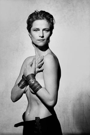 Charlotte Rampling, her arms across her naked chest, large bangles on her wrists