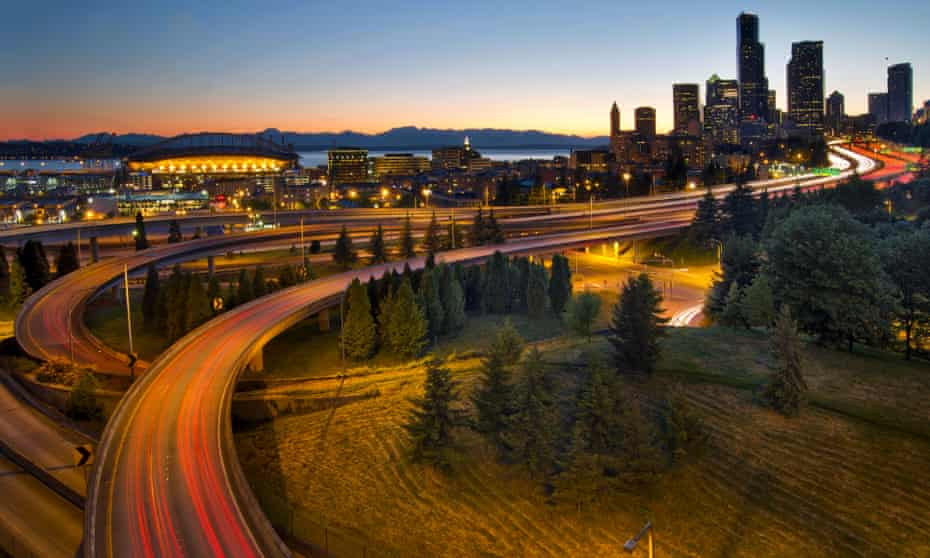 Cars drive along the Seattle Interstate 5 highway at sunset.