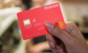 A woman's hand holding a red Monzo card