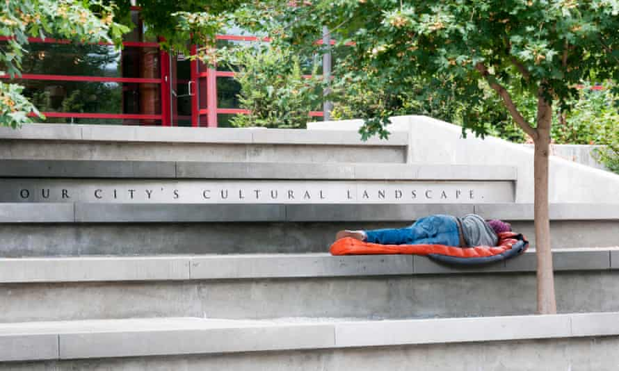 A homeless man sleeps on steps at the Seattle Center