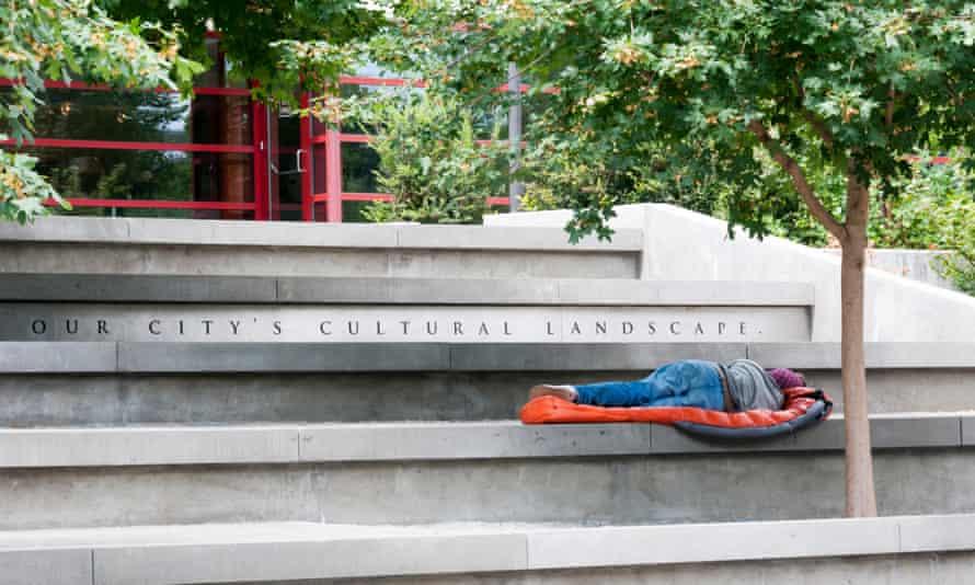 A homeless man sleeps on steps in Seattle.