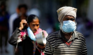 People wearing protective masks queue for food in New Delhi, India.