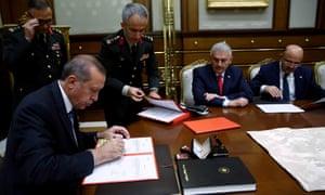 Turkish president Recep Tayyip Erdoğan signing the state of emergency decree in Ankara.