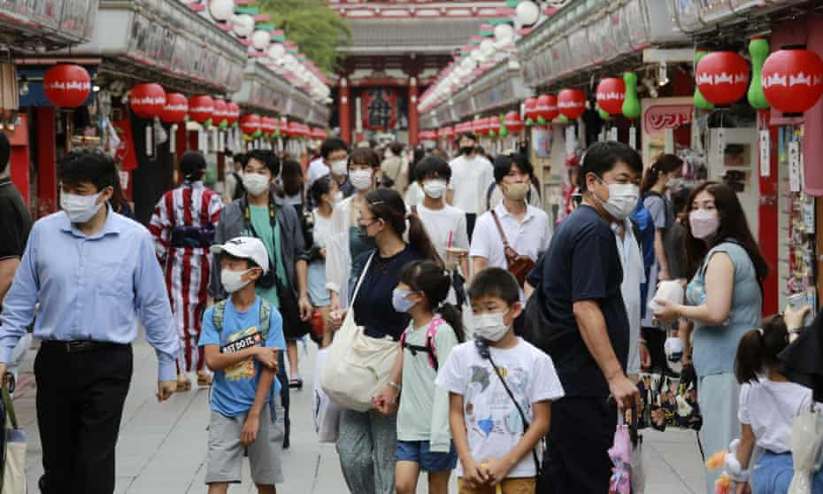 People wearing face masks to protect against the spread of the coronavirus walk Asakusa Nakamise shopping street in Tokyo, Japan