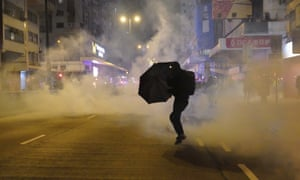 A protester holds an umbrella as police fire teargas during a New Year's Eve demonstration in Hong Kong.