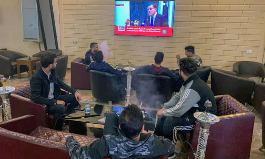 People watch Libya's newly-elected prime minister Abdelhamid Dbeibah speaking on a TV screen at a cafe in Misrata