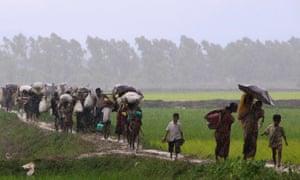 Rohingya refugees from Rakhine state in Myanmar walk along a path in the rain