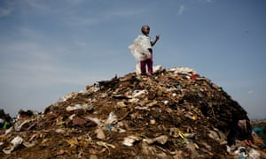 A young boy stands on top of a rubbish dump at the side of the road in Kibera Slum in Nairobi, Kenya