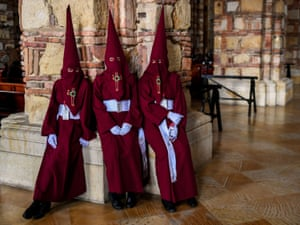 Members of Nazarenos brotherhood take a rest after participating in the traditional Lord's Passion procession in Zipaquira, Colombia.