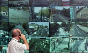 A Metropolitan police officer watches a bank of monitors showing images from London's CCTV camera network.