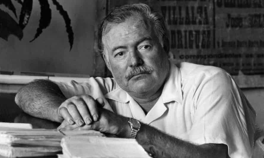 Ernest Hemingway leaning on the desk of his office
