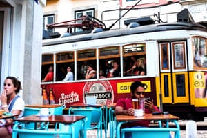 An iconic scene in Lisbon, as Tram 28 rumbles past a street cafe