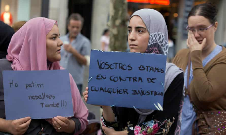 Two women hold placards that read 'We suffered it too' and 'We are against any injustice' at an impromptu memorial two days after a van crashed into pedestrians at Las Ramblas in Barcelona'