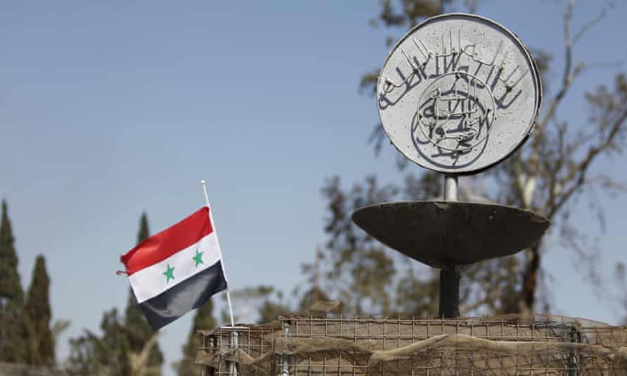 A Syrian national flag flutters next to the Islamic State's slogan