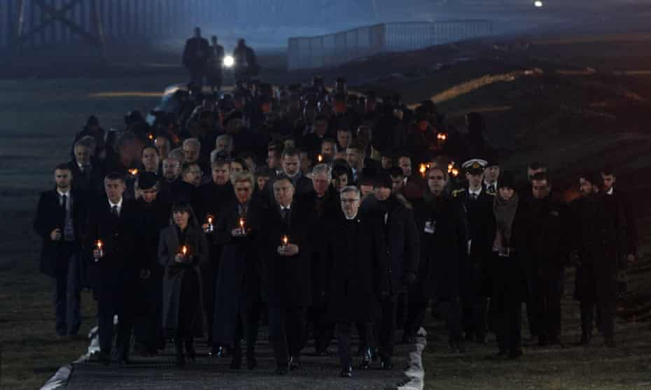Attendees arrive to put candles at a memorial site at the Auschwitz camp.