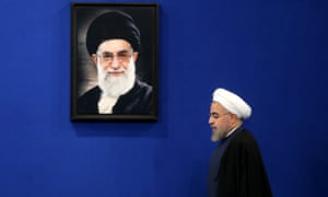 The Iranian president, Hassan Rouhani, walks under a picture of the supreme leader, Ayatollah Ali Khamenei