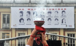 A woman burns incense during a ceremony to mark the 30th anniversary of the siege of the Palace of Justice in Bogotá on 6 November 2015 before a banner declaring: 'No more impunity.'