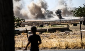 A boy looks on as smoke rises close to the Syrian-Turkish border town of Jarabulus