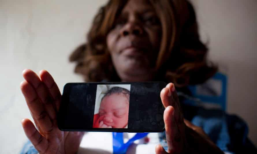 Midwife Pamela Dochieng holds up her phone to show a photo of a baby that was delivered and then abandoned at a clinic in Kibera.