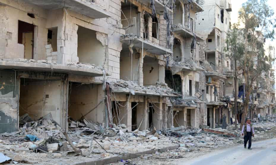 A man walks past damaged buildings in Aleppo