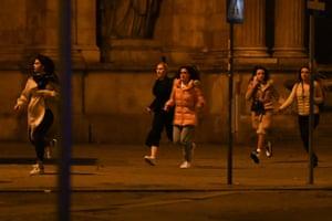 Women run away after a shooting near a synagogue in Vienna, Austria