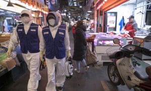 Disinfection workers sterilise an area in Tong-in Market, central Seoul.