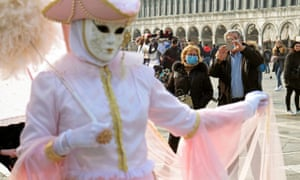People wear protective face masks in St Mark's Square after the last days of Venice carnival were cancelled due to coronavirus.