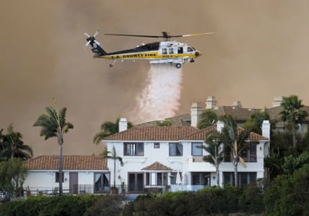 A helicopter drops water on a brush fire during the Woolsey Fire in Malibu, California.