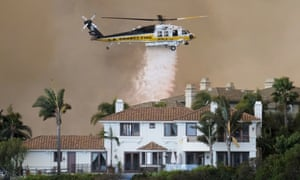 A helicopter drops water on a brush fire behind a home during the Woolsey fire in Malibu.