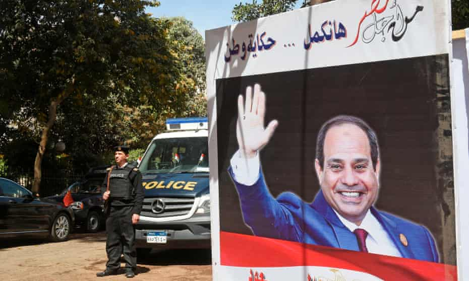 Police stand guard outside a polling station with an electoral banner depicting President Abdel Fatah al-Sisi