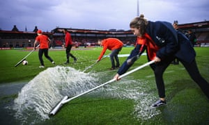 Ground-staff clear water from the pitch after heavy rain prior to the quarter-final between Germany and Denmark at Sparta Stadion in Rotterdam.