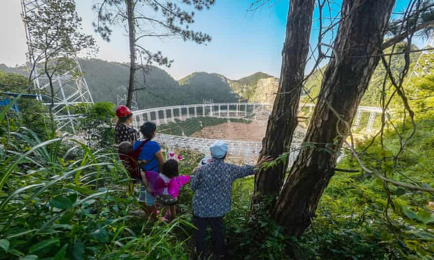 Local villagers look at the construction site of the Aperture Spherical Telescope.