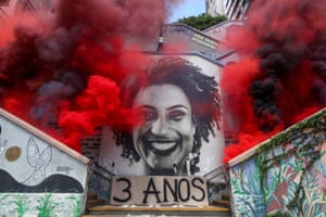 Smoke is released by an antifascist near an image of human rights activist Marielle Franco to mark the third anniversary of her murder in Sao Paulo, Brazil, on 14 March 14.