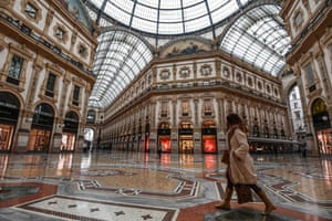 A woman walks across the deserted Galleria Vittorio Emanuele II shopping centre in Milan