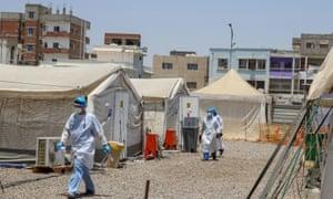 Health workers walk at a coronavirus disease quarantine center in Aden, Yemen March 27, 2021.