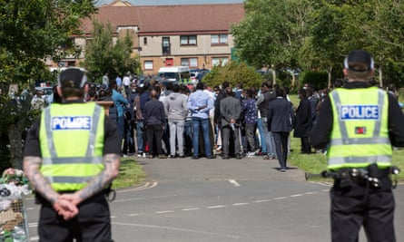 Police stand guard during the funeral of Badreddin Abedlla Adam in Glasgow