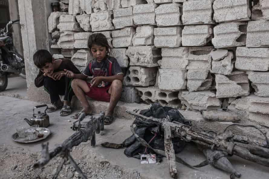 Children look at seized weapons from Islamic State on 6 September 2015 in Kobane, northern Syria