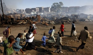 Residents of Mathare slum flee after homes and businesses were burned in a wave of violence in Nairobi following elections on 30 December 2007.