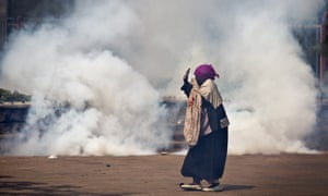 A woman caught up in the clashes holds her hands in the air as riot police approach amid clouds of teargas during the protest in Nairobi.